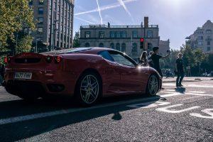 En rød Ferrari holder i et lyskryds for rødt lys , men s nogle unge tager en selfie foran den i strålende solskinsvejr.