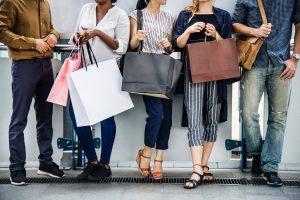 En gruppe mennesker står med flere forskellige bæreposer